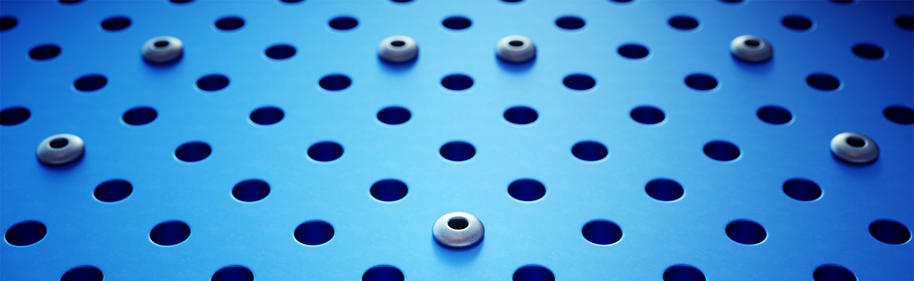 A frontal view on an artificial industrial surface, dotted with circular holes and rivets. The image has an 16:9 aspect ratio.