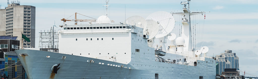 A sea level view of a military vessel with satellite dishes used in tracking rocket trajectories docked on the Halifax Waterfront.