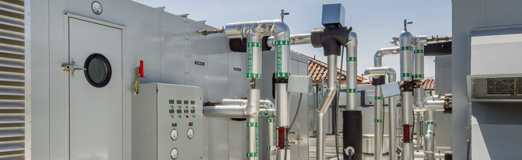 Rooftop installation for a large commercial building with filter cabinets, cooling towers and associated plumbing.