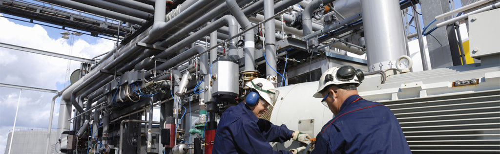 engineers working on pipeline machinery inside oil refinery.