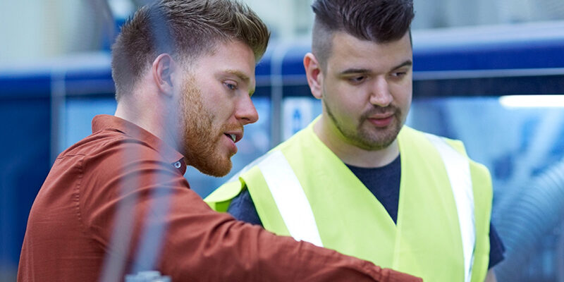 Manager giving work instructions to worker at factory shopfloor